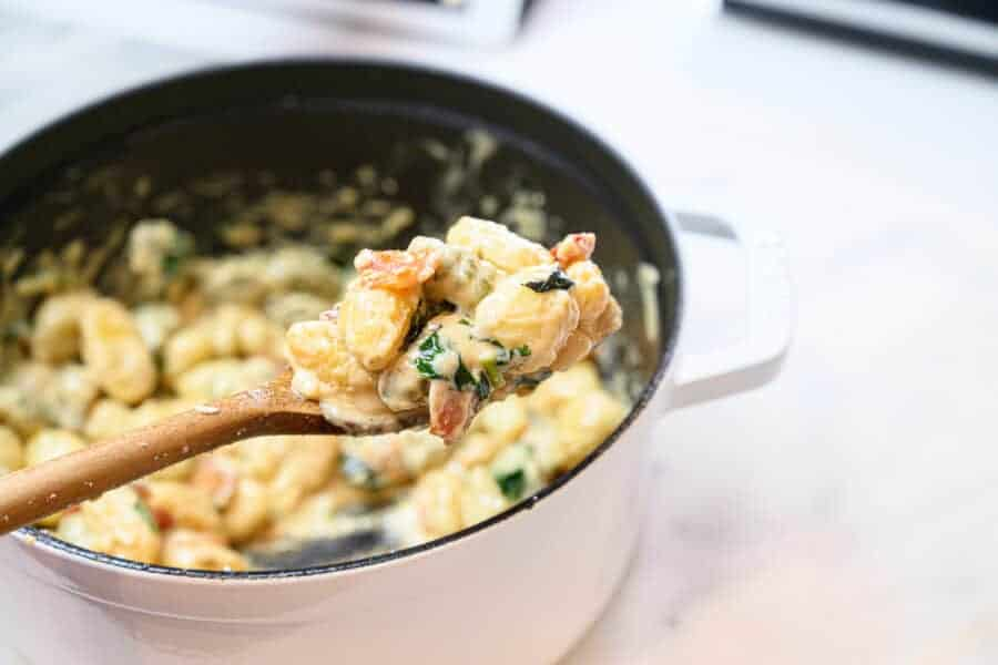 gnocchi in a dutch oven pan scooped with a wooden spoon