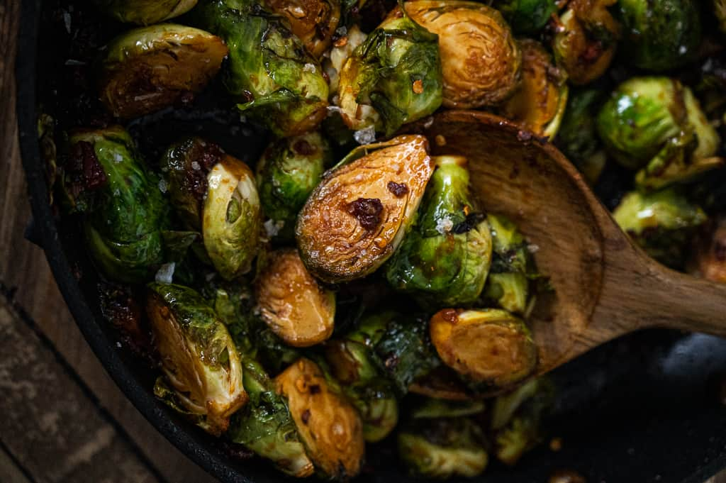 Gochujang brussels sprouts with pancetta in a pot with a wooden spoon