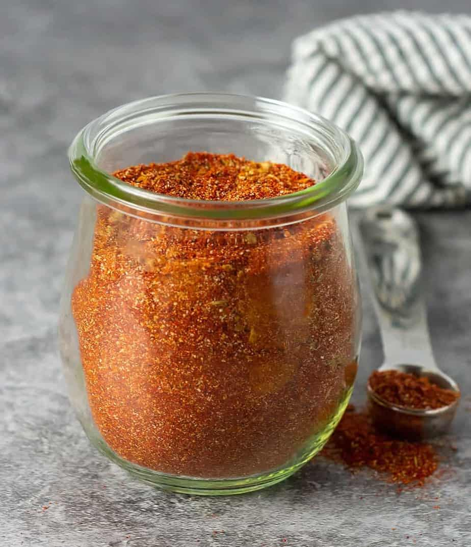 homemade chili powder blend on a tablespoon and in a glass jar.