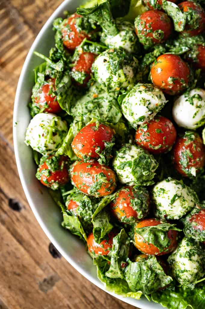 Kale Caprese Salad with wooden table in the background.