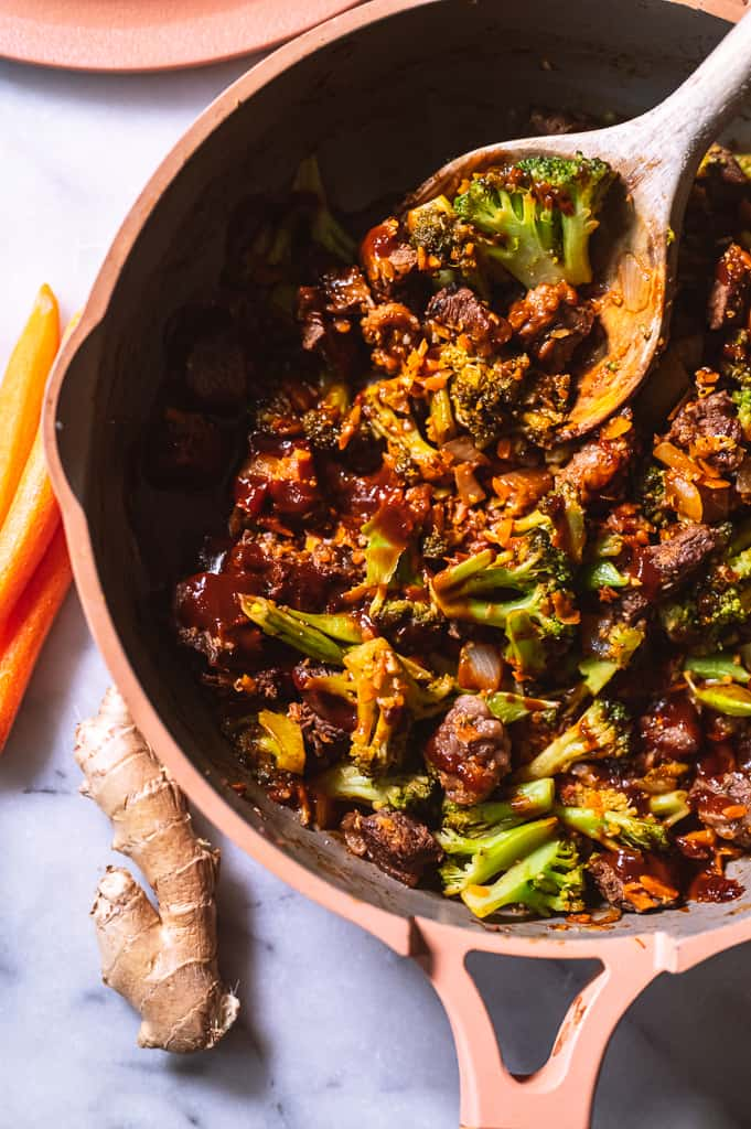 Beef and broccoli in a pan with a wooden spoon next to carrots and ginger