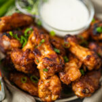 sticky miso wings on a plate with ranch dressing