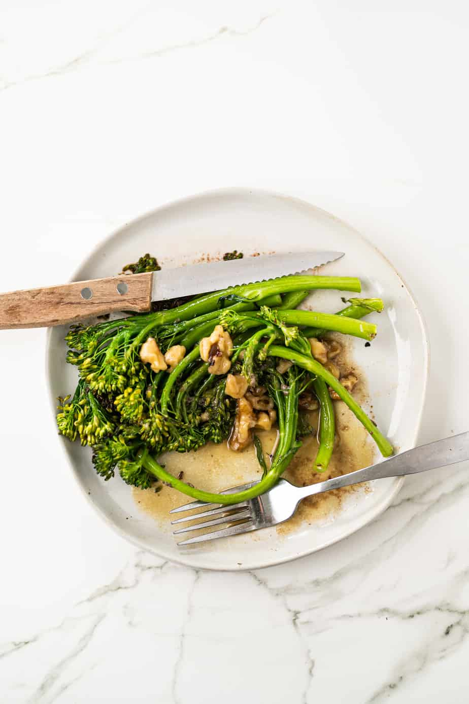 broccolini on a plate on marble with walnuts and vinaigrette