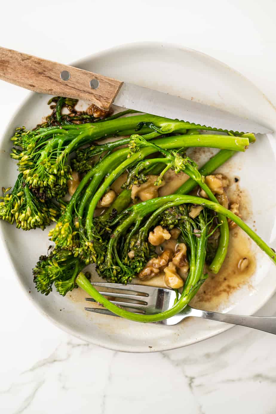 Above shot of broccolini on a plate on marble with walnuts