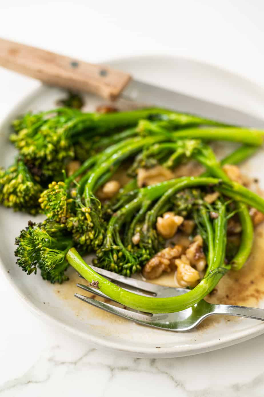 broccolini on a plate with a fork
